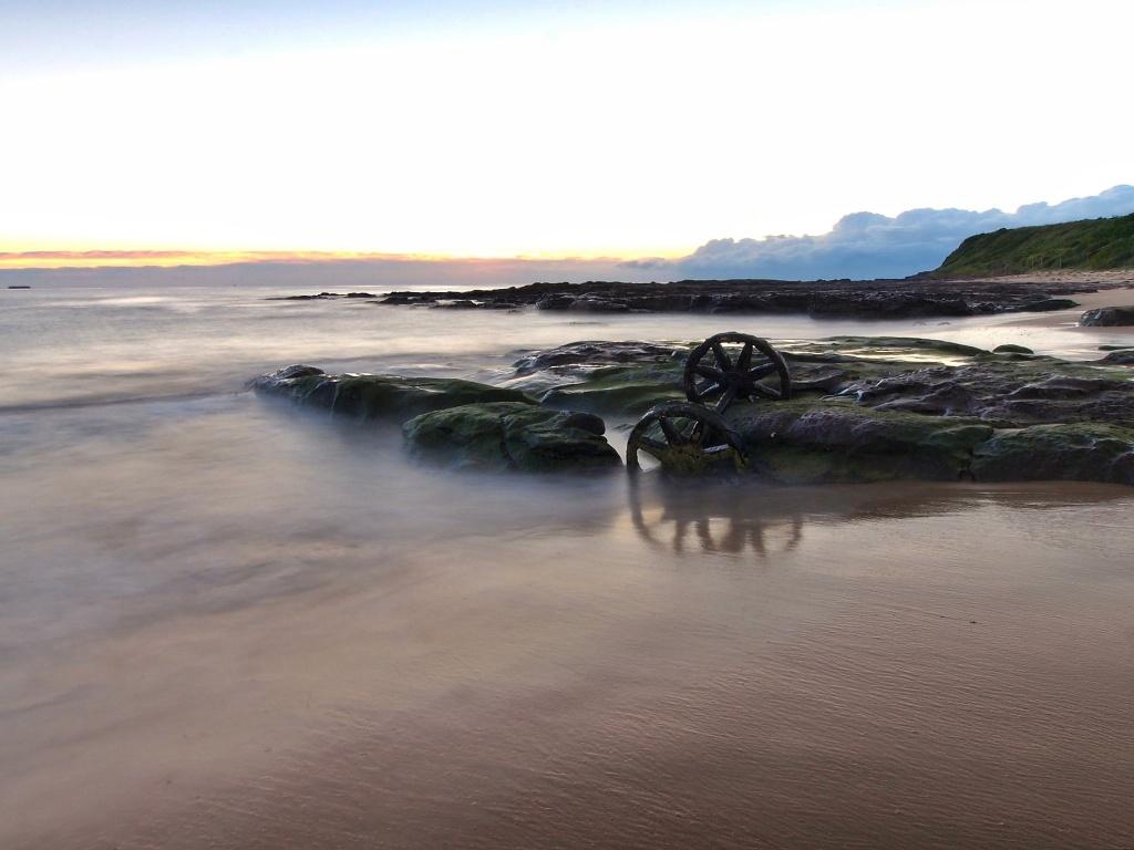 Wheels in the tide - dawn by peterdegraaff