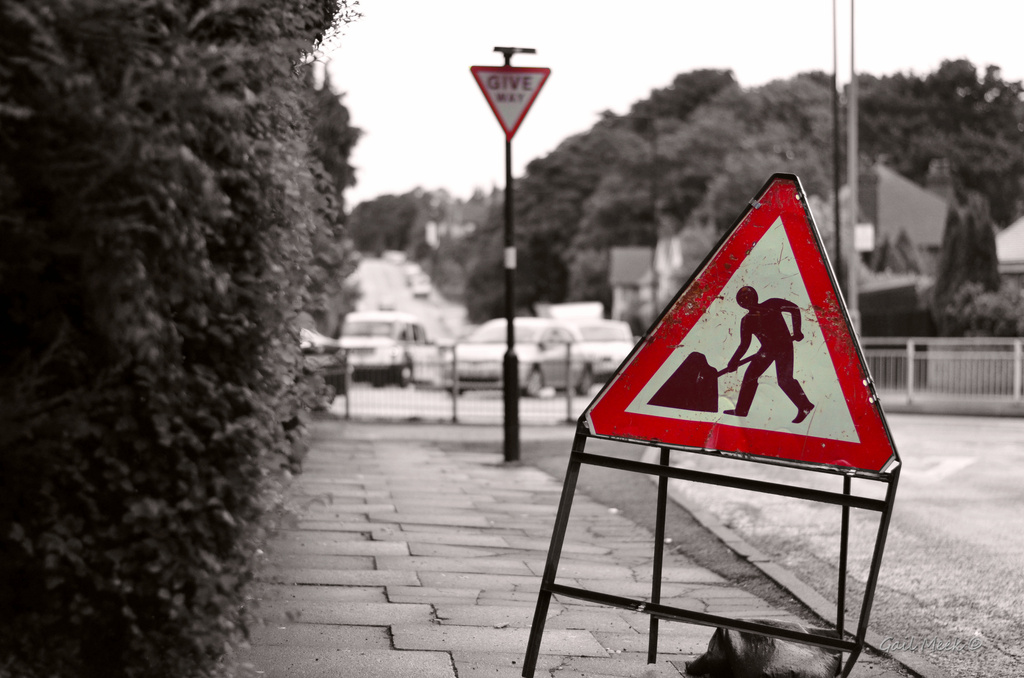 Give Way... Man with heavy umbrella crossing ahead. by gailmmeek