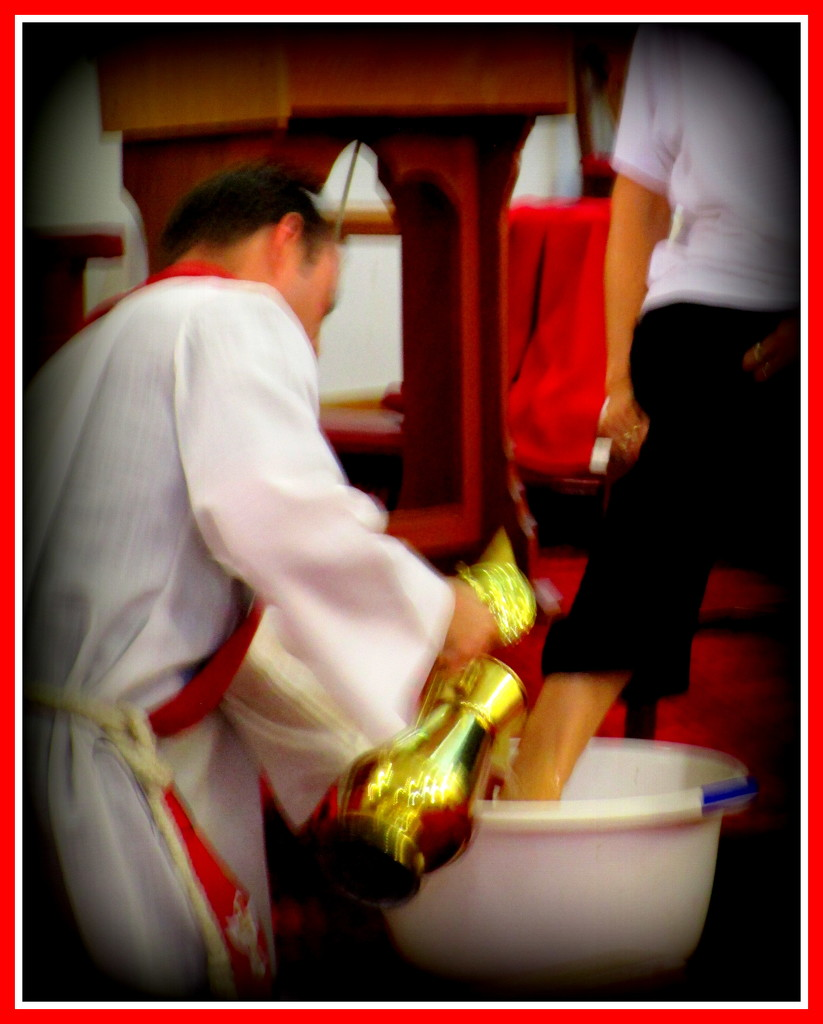 Father James washing the feet of one of the congregation. by 777margo