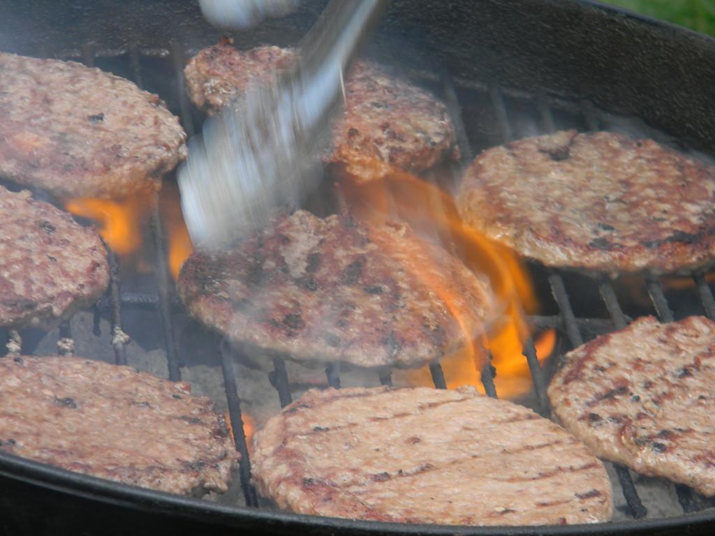 Burgers on Grill Fire Burning by sfeldphotos