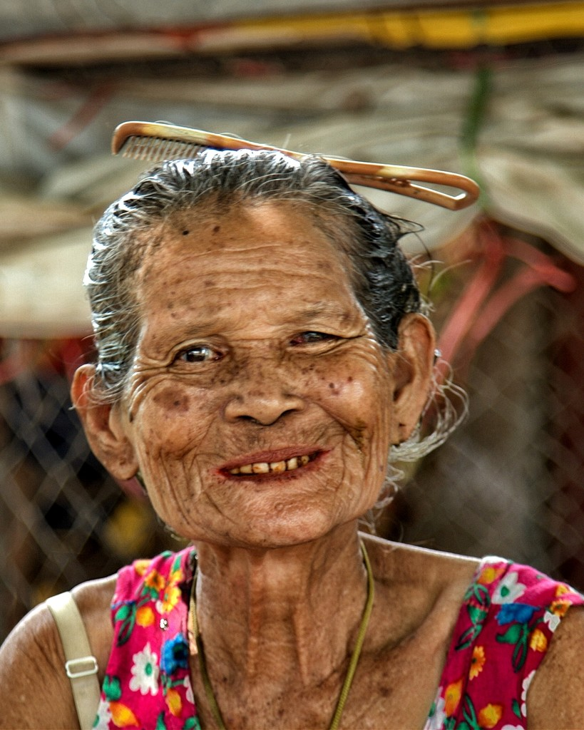 Comb in the hair and paan stained teeth. by leananiemand
