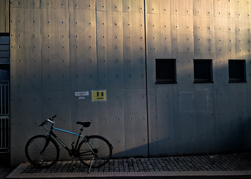 Wall, shadows and bicycle by tokyobogue