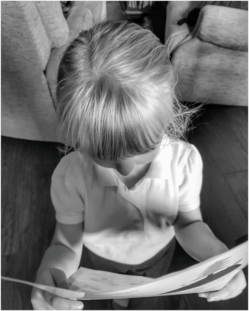 My little granddaughter reading her free book from school,.  by lyndamcg