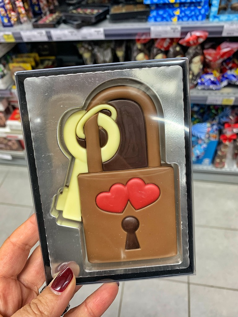 Two tiny red hearts on a chocolate locker.  by cocobella