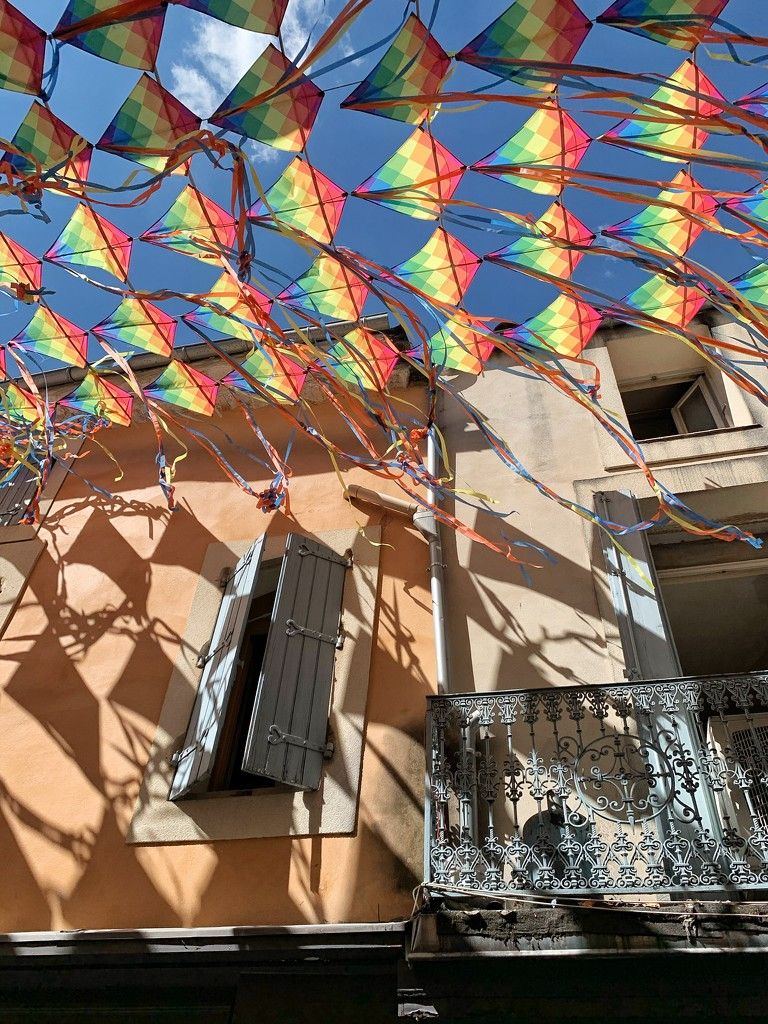 A street with kites and hearts on the balcony.  by cocobella