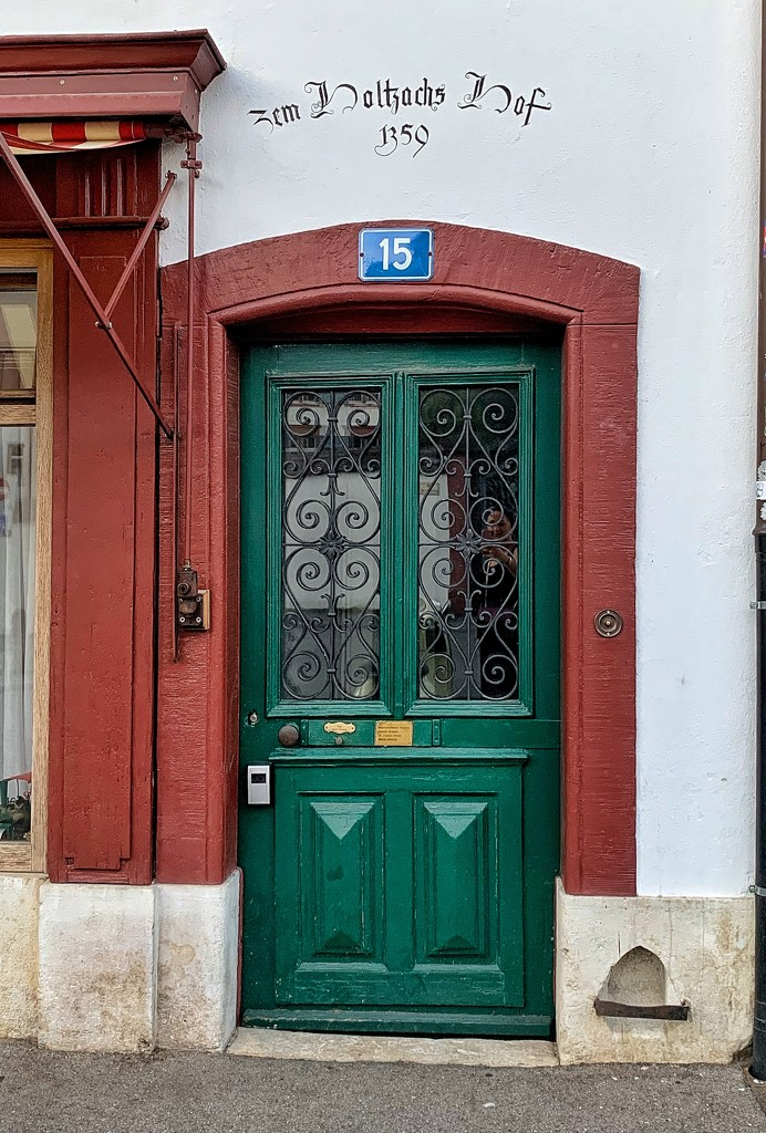 Hearts on green door under a red arch.  by cocobella
