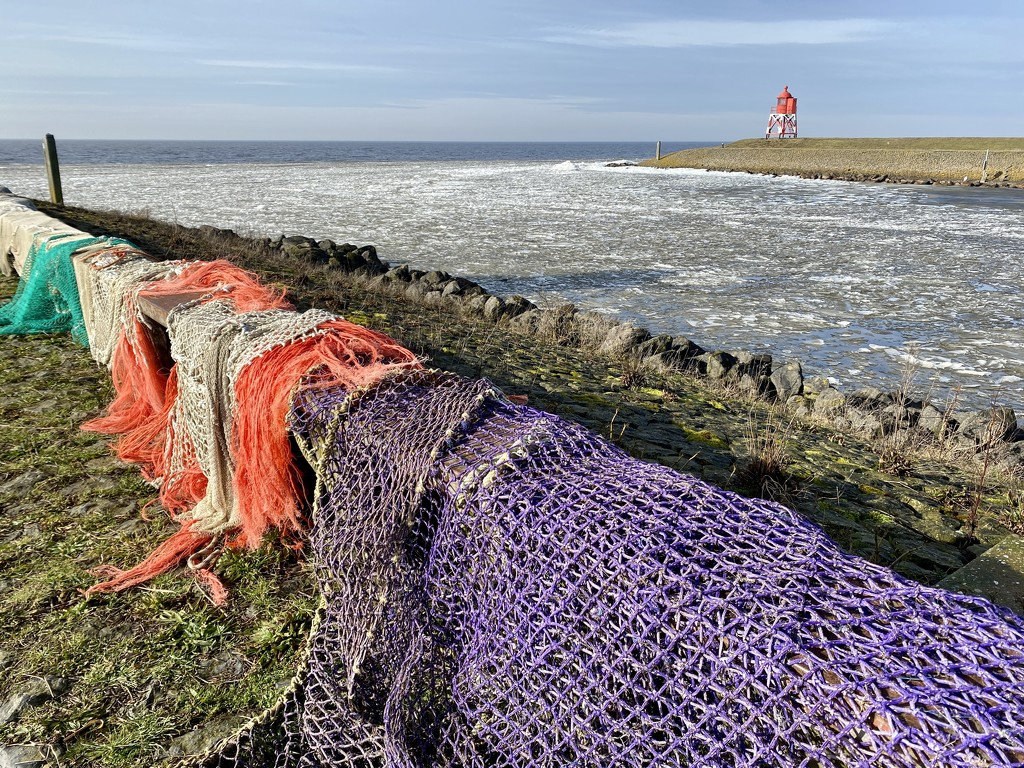 Wonderful icy waves and colorful nets in the harbour entrance by stimuloog