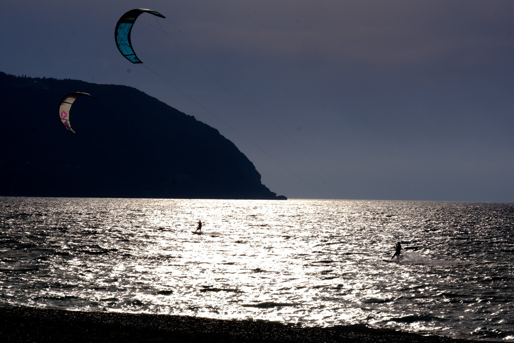 Two Kite surfers at sunset by caterina